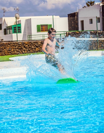 boy has fun jumping in the pool Stock Photo - 13382319