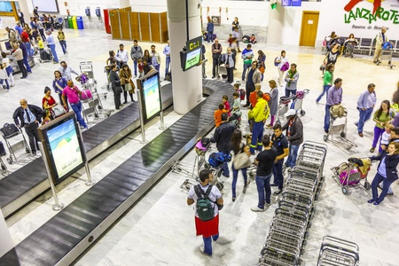 build in: ARRECIFE, SPAIN - APRIL 1: tourists wait for their baggage from Madrid at Lanzarote Airport on April 1,2012 in Arrecife, Spain. The new terminal was build in 1999 and has a capacity of 6 Mio passenger per year.