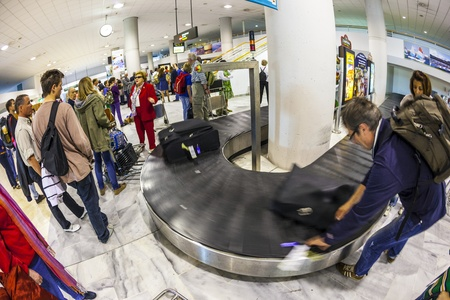 ARRECIFE, SPAIN - APRIL 1: tourists wait for their baggage from Madrid at Lanzarote Airport on April 1,2012 in Arrecife, Spain. The new terminal was build in 1999 and has a capacity of 6 Mio passenger per year.