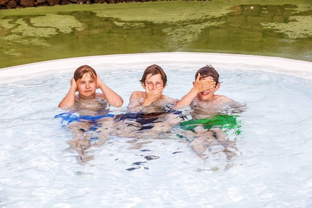 three friends in the pool imitating the three wise monkeys Stock Photo - 13369583