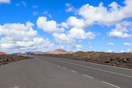 Road through lava rocks and volcanic mountains. Los Hervideros. Lanzarote photo