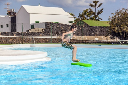 boy jumping in the pool with the surfboard photo