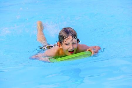 cute boy paddling on the surf board photo