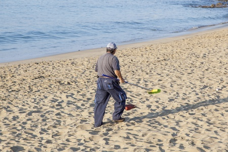 artifical: PLAYA BLANCA, SPAIN - APRIL 2: a government man cleans the beach at  April 2,2012 in Playa Blanca, Spain. The beach is artifical and the sand is shipped from Fuerteventura.