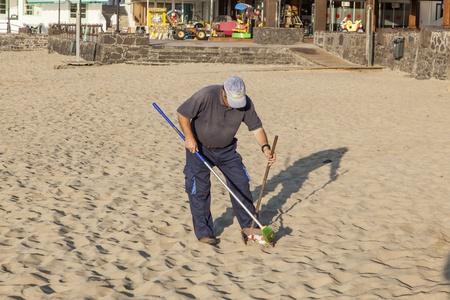 PLAYA BLANCA, SPAIN - APRIL 2: a government man cleans the beach at  April 2,2012 in Playa Blanca, Spain. The beach is artifical and the sand is shipped from Fuerteventura. Stock Photo - 13512059