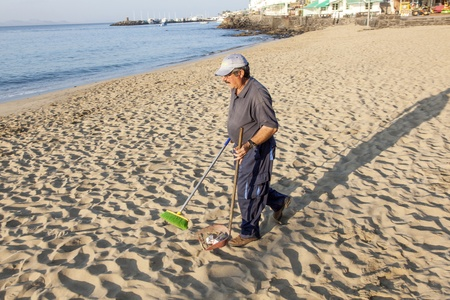 PLAYA BLANCA, SPAIN - APRIL 2: a government man cleans the beach at  April 2,2012 in Playa Blanca, Spain. The beach is artifical and the sand is shipped from Fuerteventura. Stock Photo - 13512061