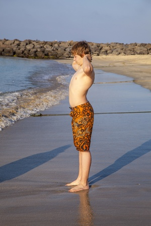 boy enjoys the beach in morning sun photo