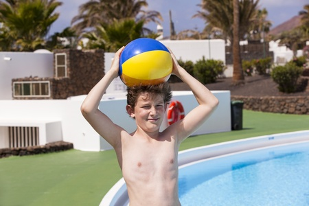 cute boy carrying a plastic ball on his head in the pool Stock Photo - 13501726