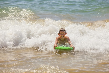 cute boy surfing in the waves photo