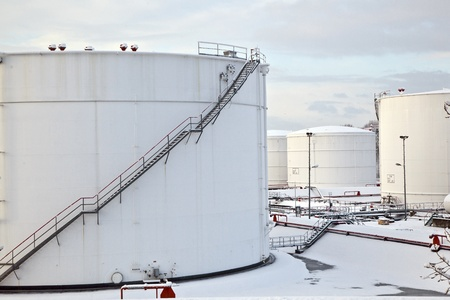 white tanks in tank farm with iron staircase in snow photo