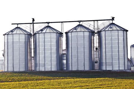 silver silos in the field photo