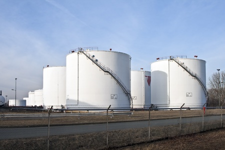 oil refinery: white tanks in tank farm with blue sky Stock Photo