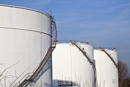 white tanks in tank farm with blue sky photo