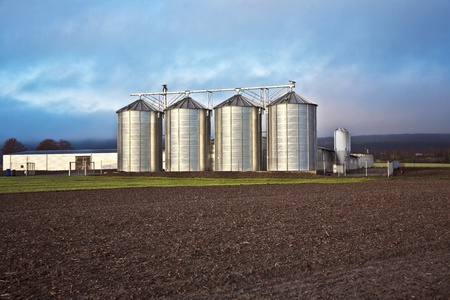 Silo in beautiful landscape with dramatically light placed in ploughed acres photo