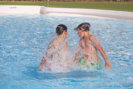 cute boys playing together in the pool Stock Photo - 13567618
