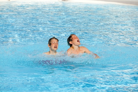 cute boys playing together in the pool Stock Photo - 13567614