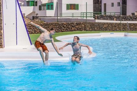 boy has fun jumping in the pool Stock Photo - 13576964