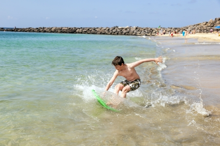 happy boy enjoys surfing in the waves at the beach Stock Photo - 13658080