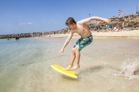 happy boy enjoys surfing in the waves at the beach Stock Photo - 13658063