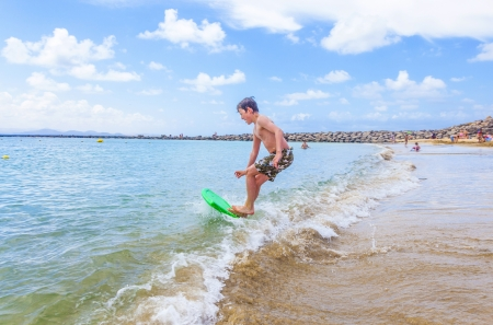 happy boy enjoys surfing in the waves at the beach photo