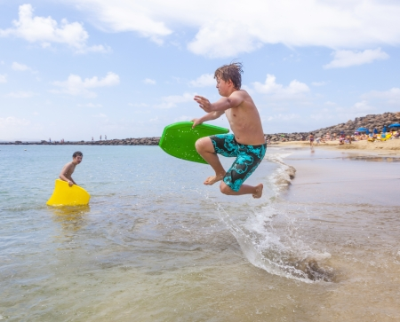happy boy enjoys surfing in the waves at the beach Stock Photo - 13658050