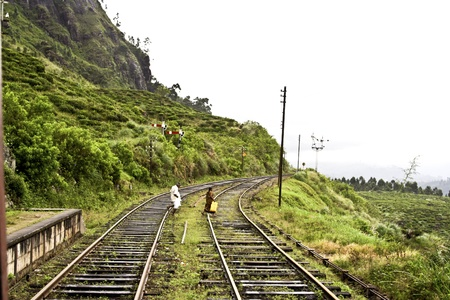 people walking on the rails of the railway in the highlands photo