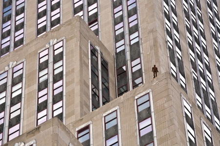 facade of Skyscraper with iron statue of man on the roof photo