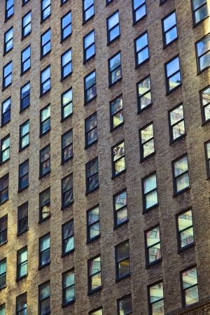 facade of old skyscraper with reflections in the windows photo
