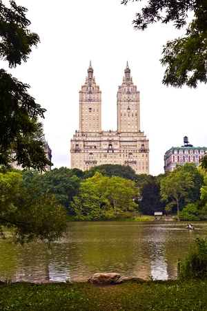 Central park in New York City Manhattan with trees and skyscrapers with lake in rain