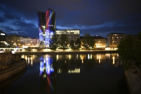 glass front of the Uniqa tower in vienna illuminated with different colors ans special effects by night, Vienna Stock Photo - 13776137