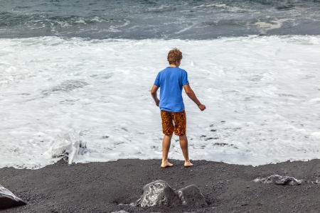 boys have fun at the black volcanic beach Stock Photo - 13688017