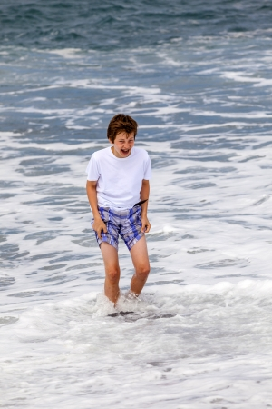 boy has fun in the spume at the black volcanic beach photo
