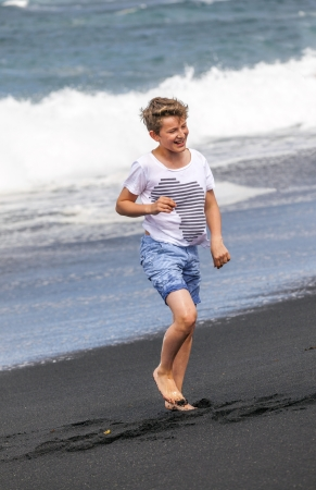 spume: boy has fun in the spume at the black volcanic beach Stock Photo