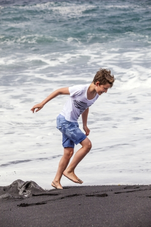 barefoot teens: boys have fun at the black volcanic beach