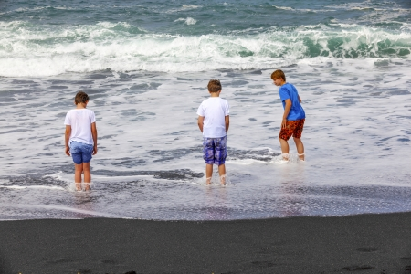 boys have fun at the black volcanic beach photo