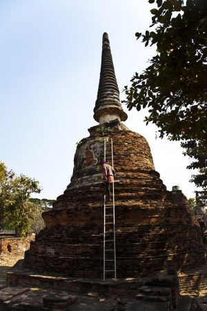 ajutthaya: worker is cleaning the surface of famous temple area Wat Phra Si Sanphet, Royal Palace in Ajutthaya