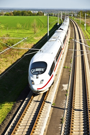railway transports: high speed train with full speed in landscape