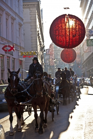 VIENNA, AUSTRIA - NOVEMBER 26: fiaker with tourists passes the decorated streets in the first district decorated with red christmas ball ornament  on November 26, 2010 in Vienna, Austria.