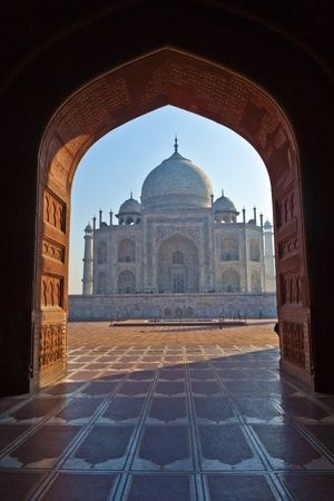 Taj Mahal in India in backlight seen from the arch of the mosque in early light photo