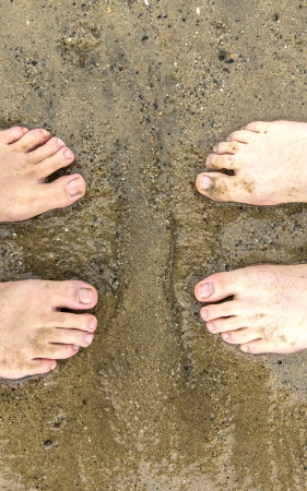 feet of father and son at the beach photo