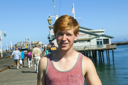 smiling attractive boy poses in front of the pier photo