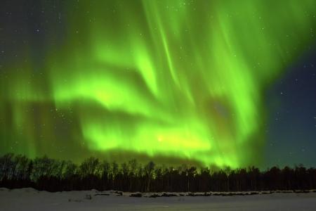 Northern Lights (Aurora borealis) over snowscape. Stock Photo