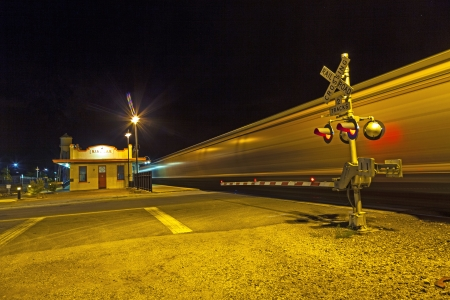 KINGMAN, AZ/USA - JUNE 14: train passes at railroad crossing in the night on June 14,2012. The Kingman station of the Santa Fee railroad opened in 1907 and is still in use. Stock Photo - 14755867