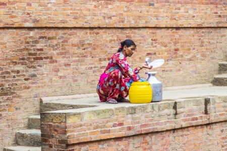 local supply: BHAKTAPUR, NEPAL- JUNE 16 : An unidentified Nepali woman fills up the water bottle with drinking water on June 16,2012 in Bhaktapur, Nepal. Bhaktapur is located about 20 km east of Kathmandu. Editorial