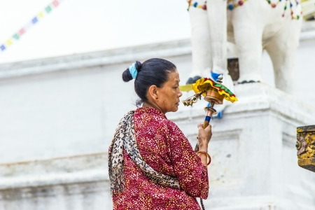 KATHMANDU, NEPAL - JUNE 17 : woman worships at bodhnath stuba on June 17,2012 in Kathmandu, Nepal. Devotees walk several times around the stupa for good luck.