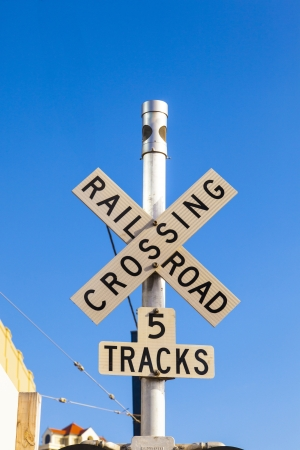 railroad crossing sign with blue sky photo