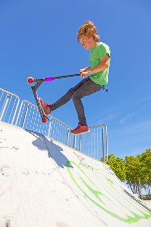boy jumps with his scooter at the skate park photo