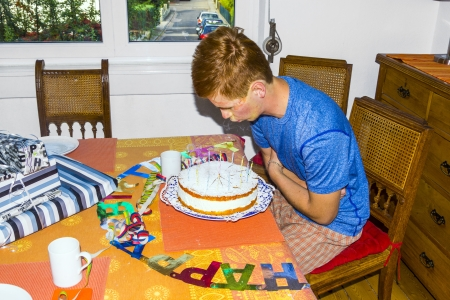 sweet seventeen: boy blowing out his birthday candles at the cake