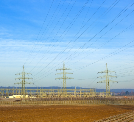 electrical tower in rural landscape with bale of straw photo