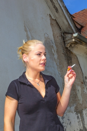 Beautiful young womansmokes a cigarette photo